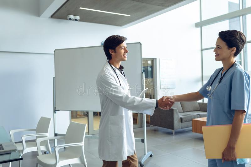 Male doctor shaking hands with female nurse in the hospital stock images