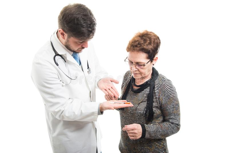 Male doctor showing diabetes shot to female senior patient royalty free stock photography
