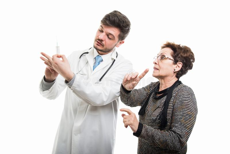 Male doctor showing syringe to female senior patient stock image