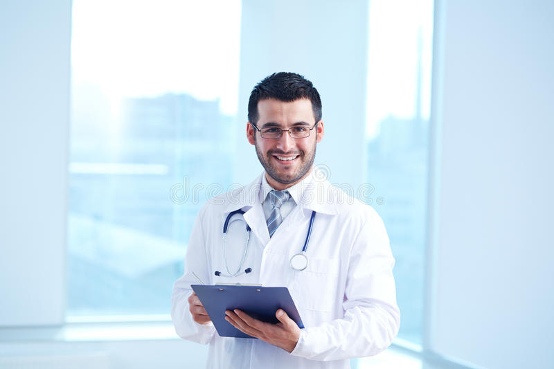 Male doctor. Smiling doctor with clipboard and stethoscope looking at camera stock photos