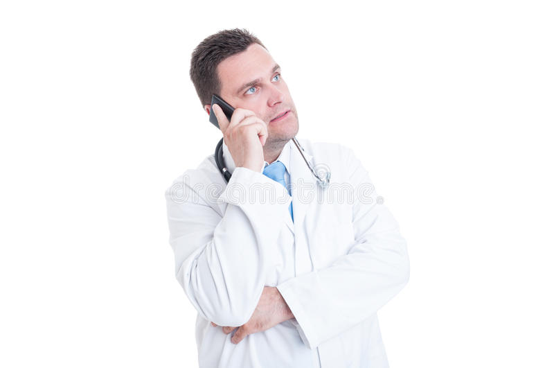Male doctor speaking at phone offering support or advice. Male doctor or medic speaking at phone offering support or advice isolated on white background with stock photo