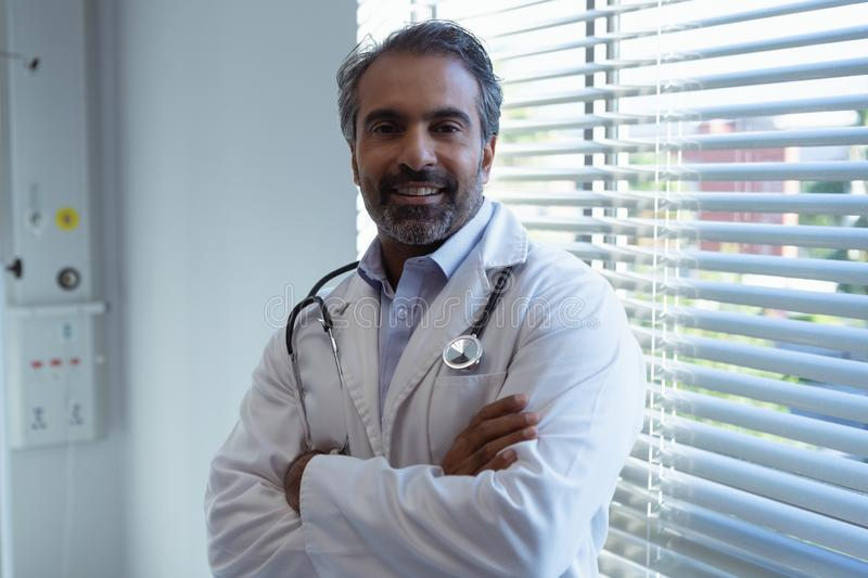 Male doctor standing with arm crossed and looking at camera in clinic at hospital royalty free stock photos