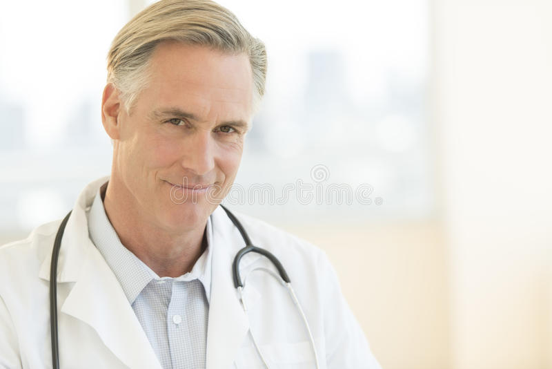 Male Doctor With Stethoscope Around Neck In Clinic. Portrait of confident mature male doctor with stethoscope around neck in clinic royalty free stock photography