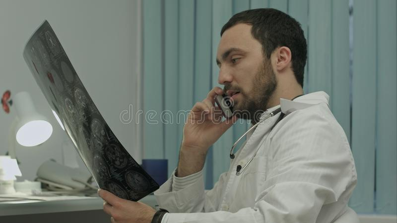 Male doctor talking on cellphone at modern hospital indoors. Handsome doctor speaking on cellphone and looking at patient`s head scanning stock photo