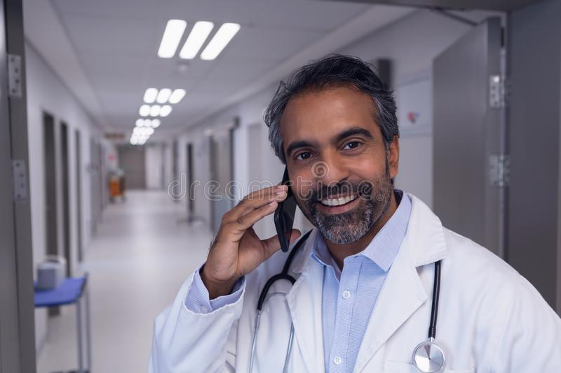 Male doctor talking on mobile phone in hospital corridor. Front view of mature mixed race male doctor talking on mobile phone in hospital corridor stock photo