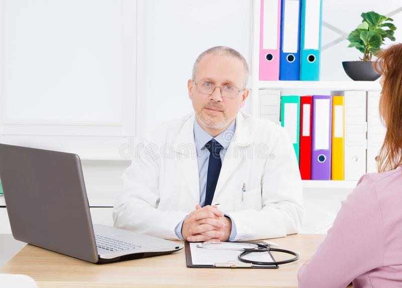 Male doctor is talking to female patient in hospital office. Healthcare and medical service. Helping people royalty free stock photos