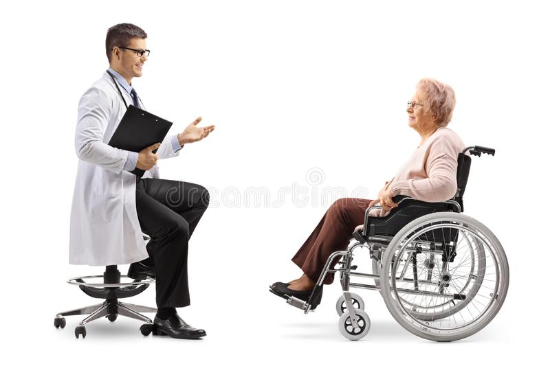 Male doctor talking to a mature female patient in a wheelchair. Full length shot of a male doctor talking to a mature female patient in a wheelchair isolated on stock photos