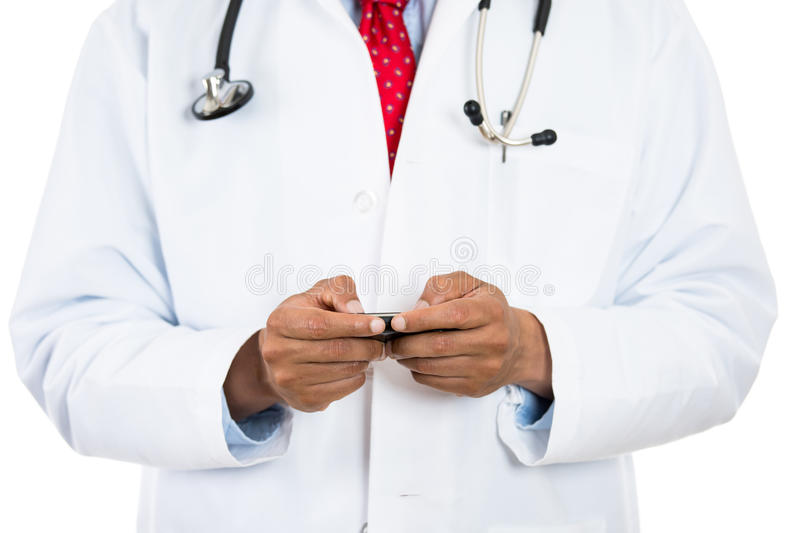 Male doctor texting on his phone. Cropped image of a male doctor texting on his phone, isolated on a white background royalty free stock photos