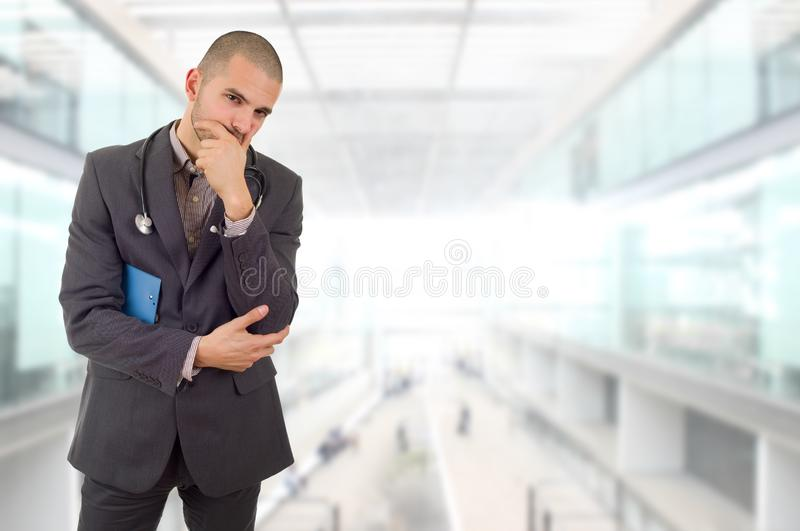 Doctor thinking. Male doctor thinking with his notes, at the hospital stock photos
