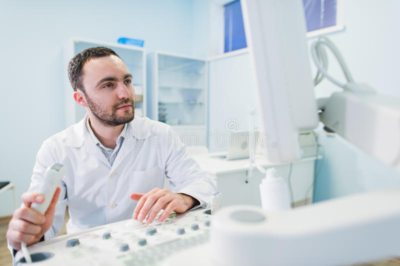 Male doctor with ultrasonic equipment during ultrasound medical examination.  stock photo