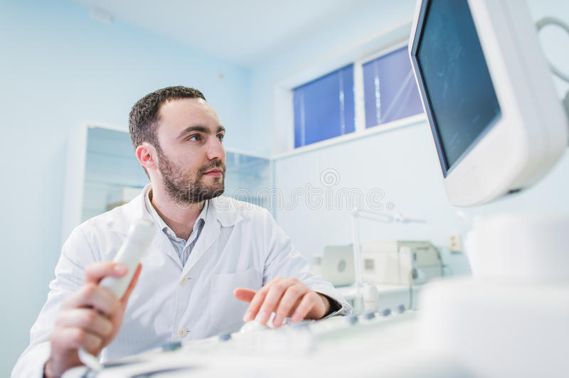 Male doctor with ultrasonic equipment during ultrasound medical examination.  royalty free stock photos