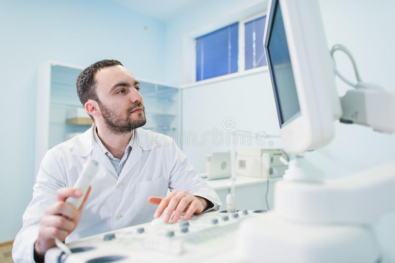 Male doctor with ultrasonic equipment during ultrasound medical examination.  royalty free stock photography