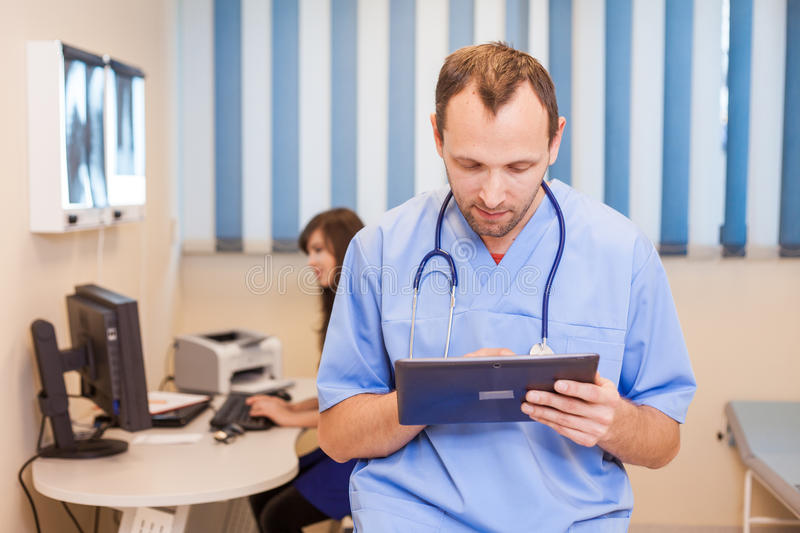 Male doctor using a tablet computer in a hospital. In a background sitting nurse. royalty free stock image