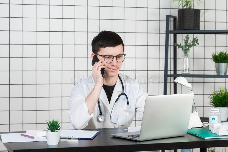 Male doctor using telephone while working on computer at table in clinic royalty free stock photo