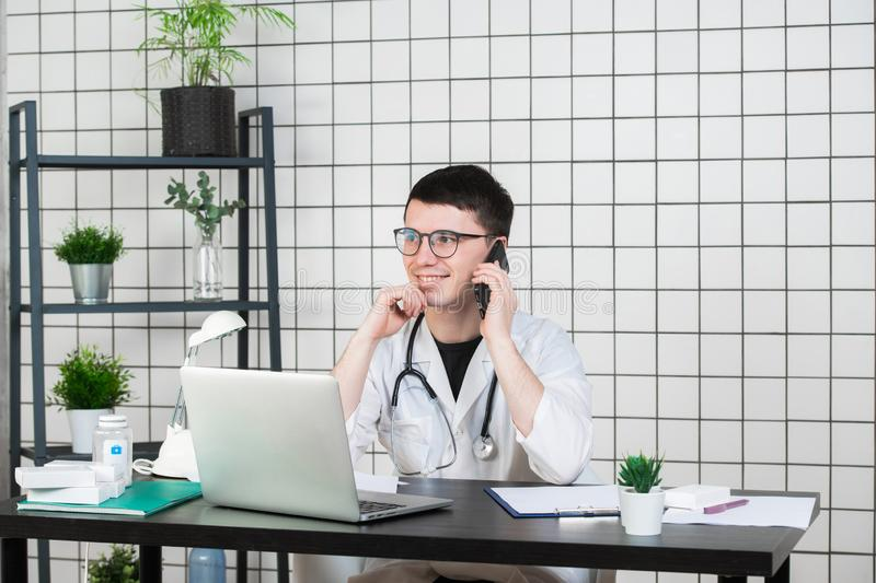 Male doctor using telephone while working on computer at table in clinic stock photos