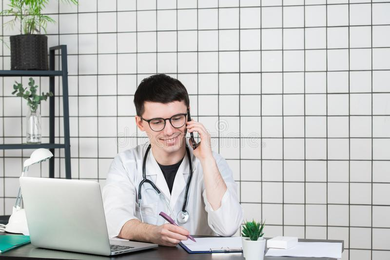 Male doctor using telephone while working on computer at table in clinic stock photography
