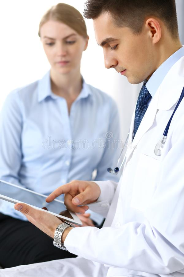 Male doctor using touchpad or tablet pc while consulting female patient in hospital office. Medicine and healthcare. Concept royalty free stock photo