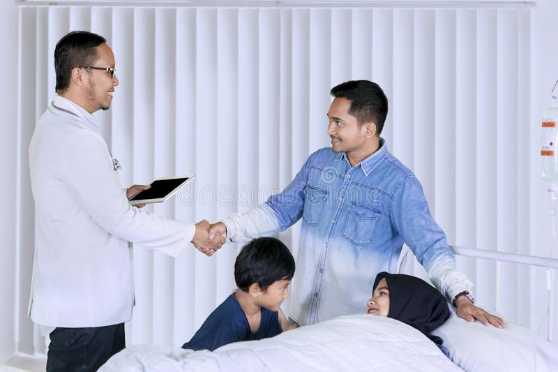 Male doctor visiting his patient family in the clinic royalty free stock photo
