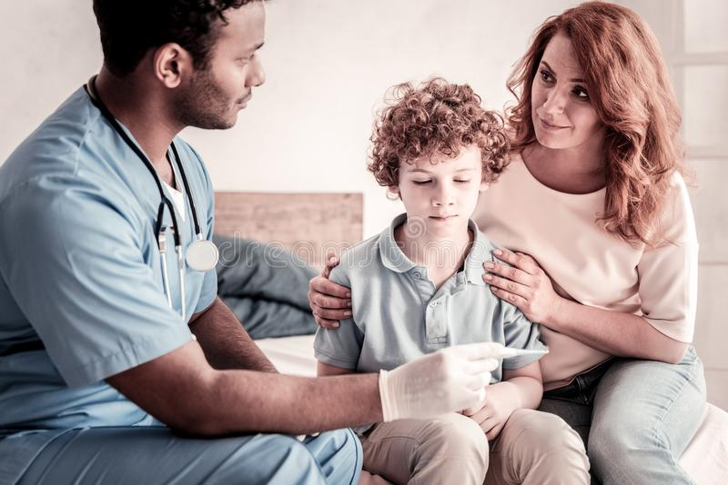 Male doctor visiting poor boy having temperature royalty free stock images