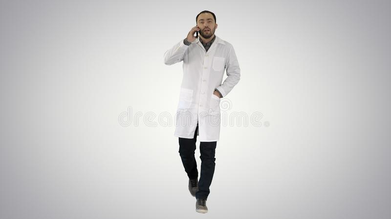 Male doctor walking and talking on the phone on gradient background. Full length portrait. Male doctor walking and talking on the phone on gradient background royalty free stock images