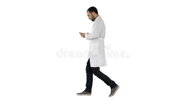 Male doctor walking and using mobile phone on white background. Full length portrait side view. Male doctor walking and using mobile phone on white background stock images