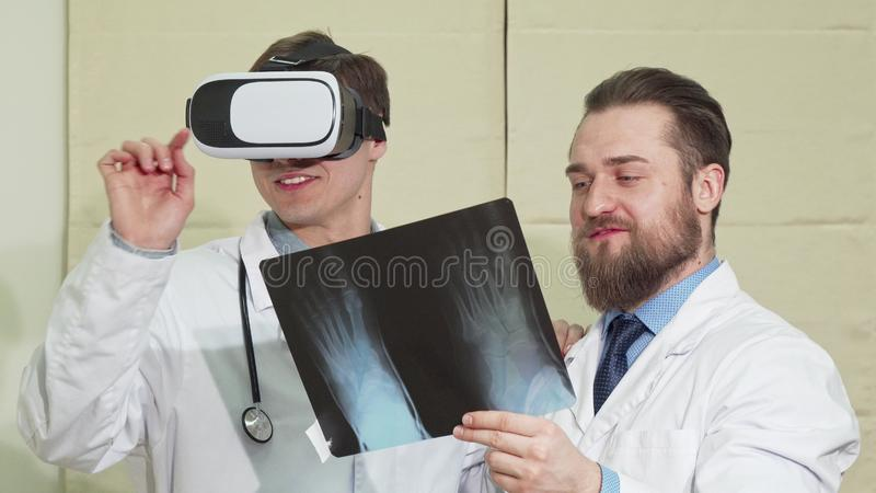 Male doctor wearing vr glasses, his colleague examining x-ray of a patient royalty free stock image