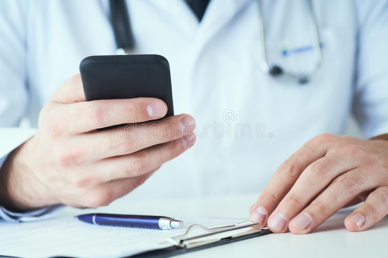 Male doctor in white coat is using a modern smartphone device with touch screen closeup. Doctor calls the patient who is stock photo