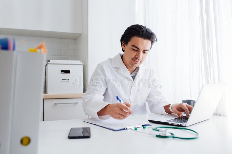 Male doctor working with laptop behind desk, writing on paperwork in a hospital. royalty free stock photo