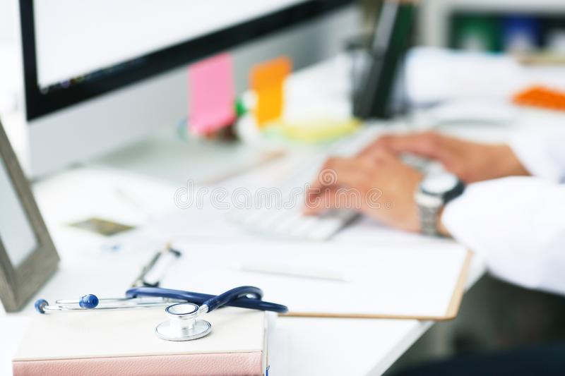 Male doctor working with laptop computer. Clipboard, pen and stethoscope on desk in hospital close-up. Male doctor royalty free stock photos
