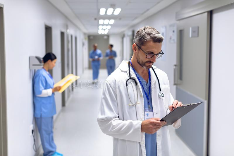 Male doctor writing on clipboard in corridor at hospital stock images
