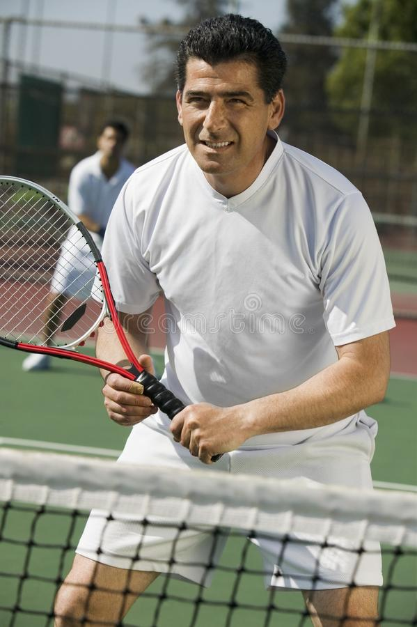 Male doubles tennis players waiting for serve. Front view, focus on foreground stock images
