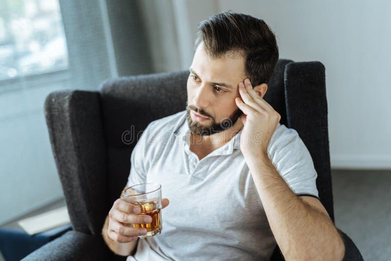Sad upset man drinking alcohol stock images