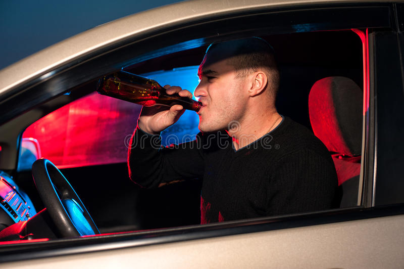 Male driver on the background of police car light. Young male driver drinking beer in car on the background of police car lighting royalty free stock photography