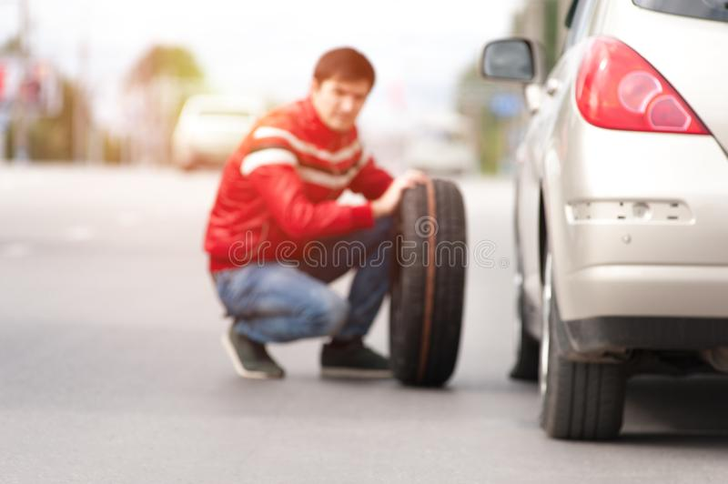 Male driver after car breakdown on cityroad. Blurred picture of young man sitting near broken car and changing tyre wheel. Male driver agter car breakdown on stock photography