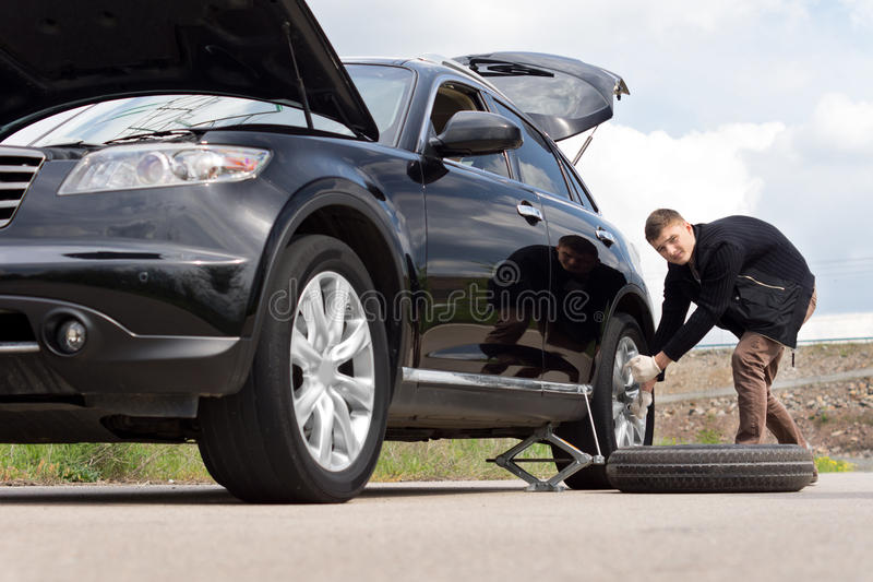Male driver changing his tyre at the roadside. Male driver changing his tyre on the car at the roadside after suffering a puncture on a rural road , low angle royalty free stock image
