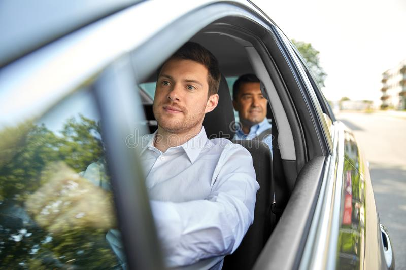 Male driver driving car with passenger. Transport, taxi and people concept - male driver driving car with passenger royalty free stock photo