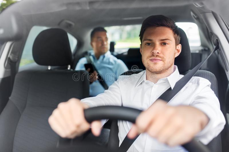 Male driver driving car with passenger stock photo