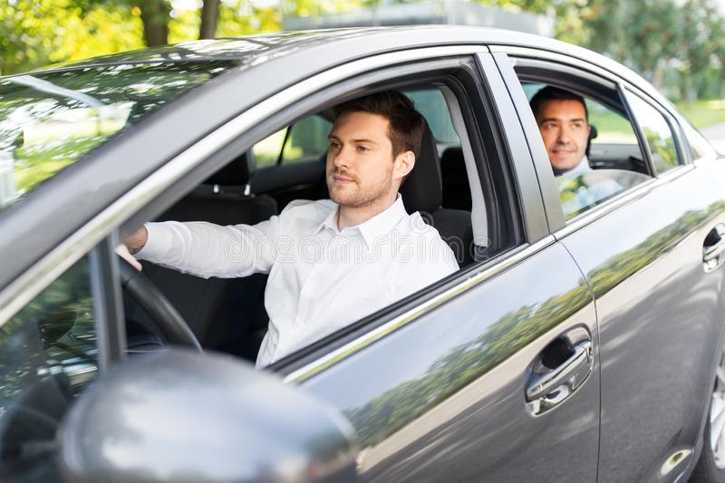 Male driver driving car with passenger. Transport, vehicle and people concept - male driver driving car with passenger stock photo