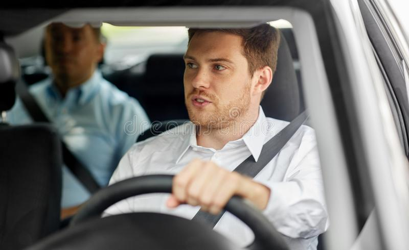 Male driver driving car with passenger. Transport, vehicle and people concept - male driver driving car with passenger stock images