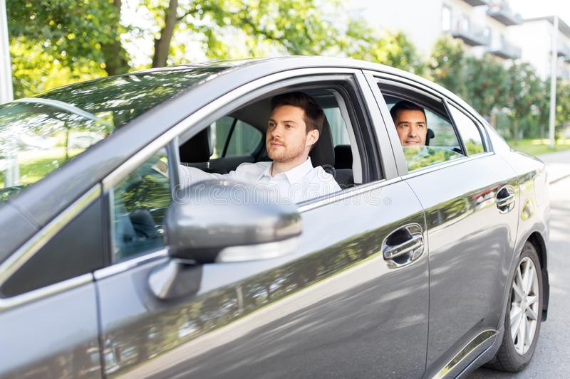 Male driver driving car with passenger. Transport, vehicle and people concept - male driver driving car with passenger royalty free stock images