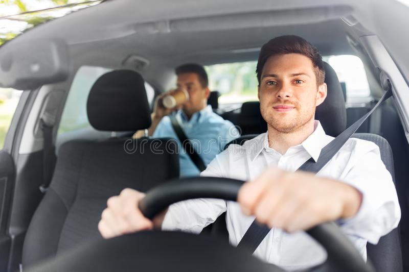Male driver driving car with passenger stock image