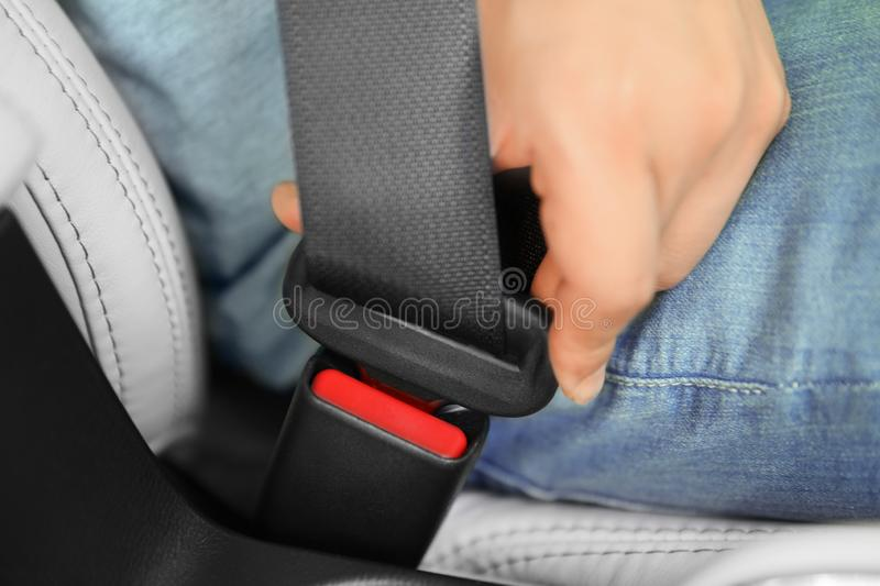 Male driver fastening safety belt in car. Closeup royalty free stock photography