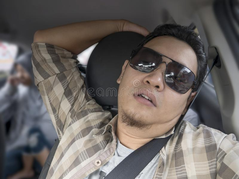 Male Driver Get Bored in His Car. Portrait of funny Asian male driver get bored in his car trapped in traffic jam, tired lazy facial expression gesture stock image