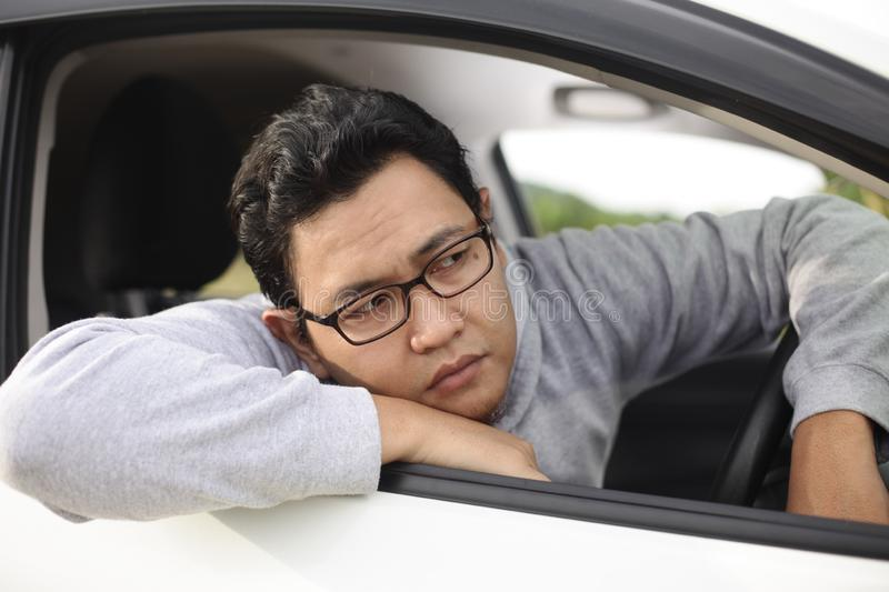 Male Driver Get Bored in His Car. Portrait of funny Asian male driver get bored in his car trapped in traffic jam, tired lazy facial expression gesture stock images
