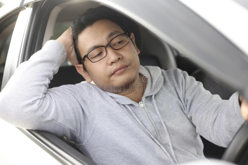 Male Driver Get Bored in His Car. Portrait of funny Asian male driver get bored in his car trapped in traffic jam, tired lazy facial expression gesture royalty free stock photo