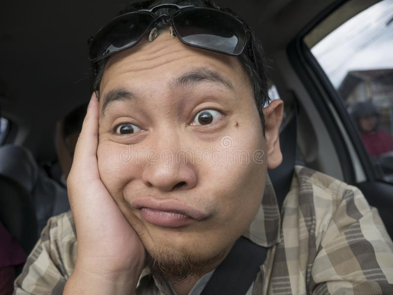 Male Driver Get Bored in His Car. Portrait of funny Asian male driver get bored in his car trapped in traffic jam, tired lazy facial expression gesture stock photography