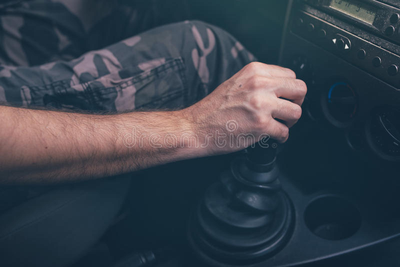 Male driver hand shifting gear manually. Selective focus stock photo