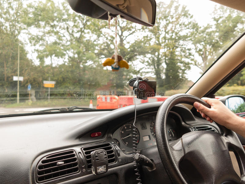 Male driver hands holding steering wheel of a car. Male driver hand holding steering wheel of a car on english road royalty free stock photo