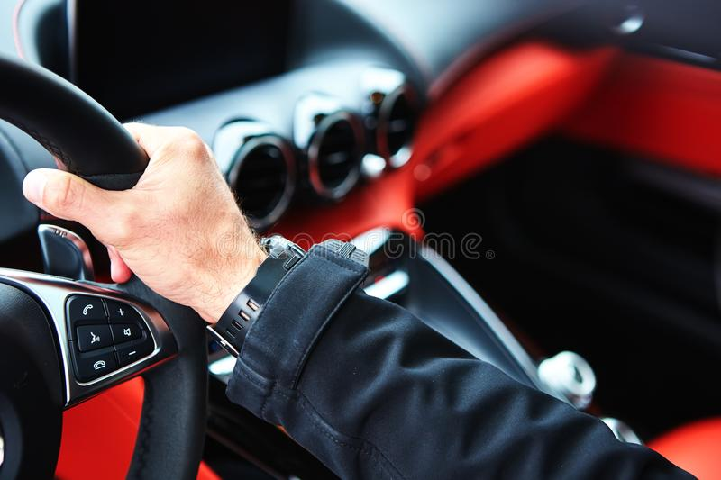 Male driver hands holding steering wheel. The male driver hands holding steering wheel stock photo