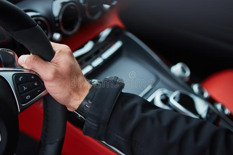 Male driver hands holding steering wheel. The male driver hands holding steering wheel stock photography